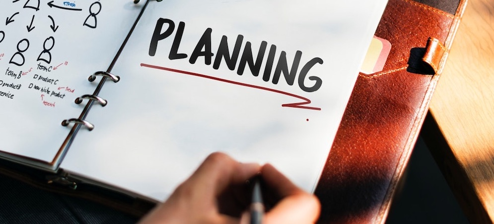 Person writing a plan in a notebook that says planning