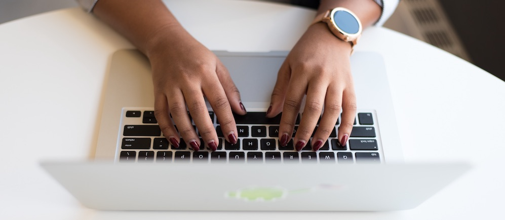 Woman wearing a gold watch typing on a laptop computer