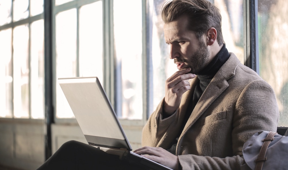 Man looking at his laptop in frustration