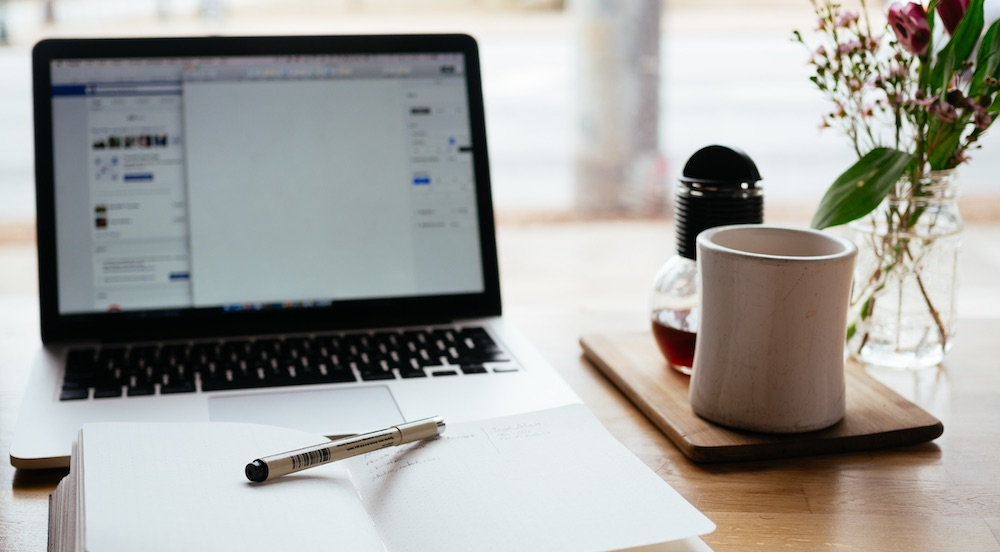 Laptop open sitting on wooden table with notebook, pen, and coffee mug