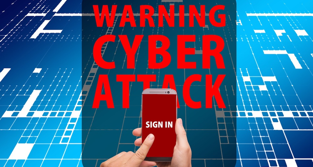 person holding cell phone that says sign in and the background says warning cyber attack