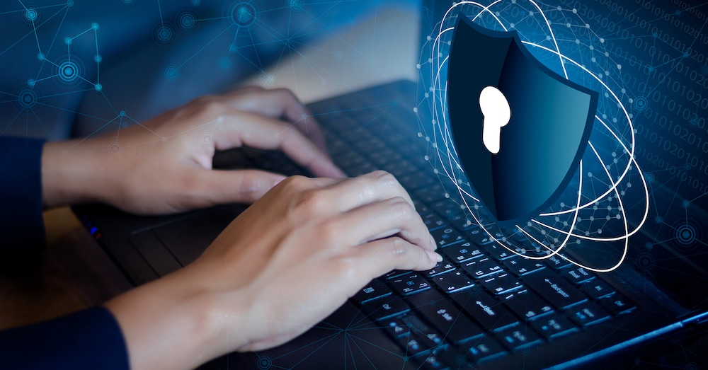 Laptop security with person typing on keywboard with a shield with a keyhole next to them