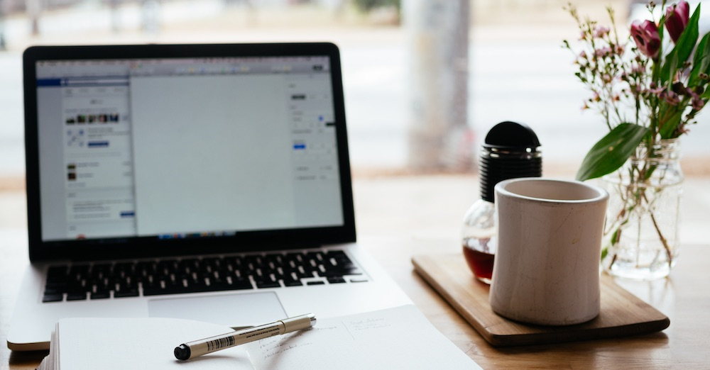 Laptop computer with notebook and pen in front of it and a coffee cup to the right