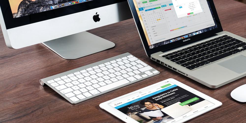 Apple tablet, laptop, and desktop computer on wooden desk