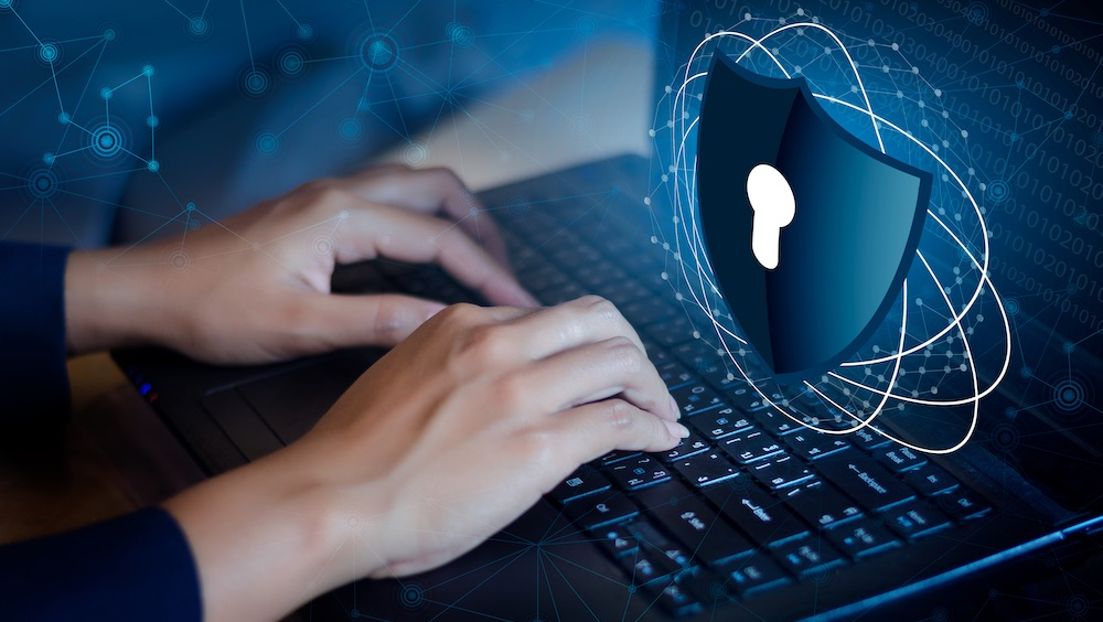 IT professional typing on laptop with a shield of keyhole image above
