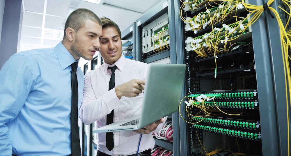 Two IT professionals in a server room looking at a laptop